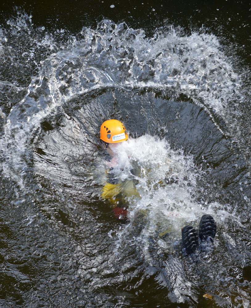 Person makes a splash during a Gorge Walking adventure in local Snowdonia mountain streams around Betws y Coed in North Wales. Image is part of the British Guild of Travel Writers Online Photography Exhibition with an Adventure theme