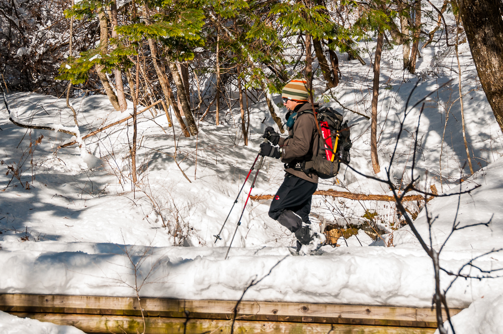 Man walking with snow shoes in the Jizo Pass along the old Hida Highway above Kiso-Fukishima, Nagano Prefecture, Japan.