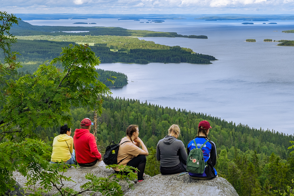 People in eastern Finland take a break from hiking along the Koli ridge to enjoy the spectacular lakeland views near the border with Russia