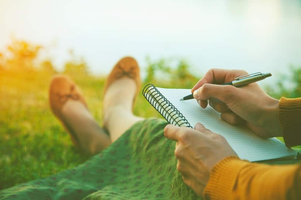 female hands with pen writing on notebook on grass outside. Journaling for self reflection