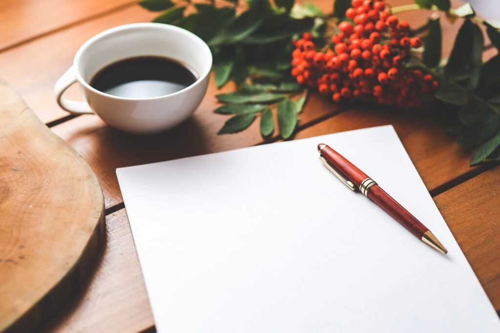 Blank piece of paper, coffee and pen. Journaling to heal