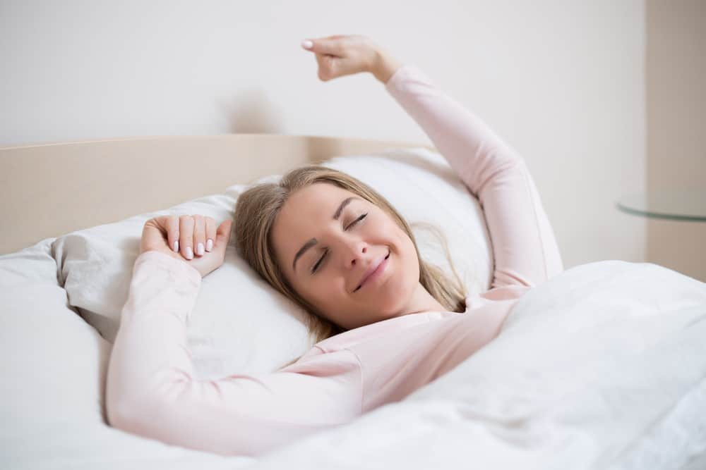Woman in bed with smile on her face. After effects of a feel-good guided meditation
