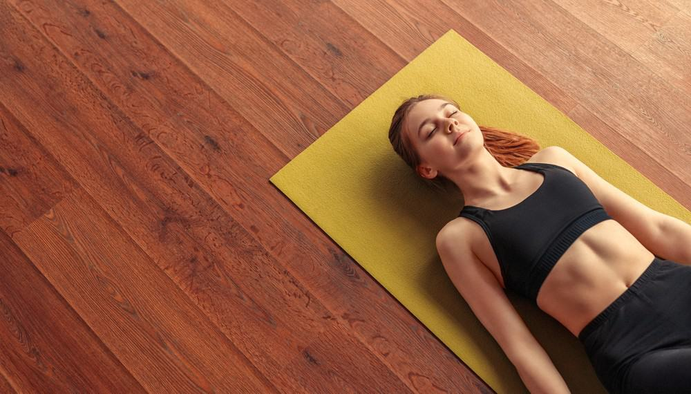 From above calm fit woman relaxing and breathing while lying at corpse pose on mat. How meditation makes you feel