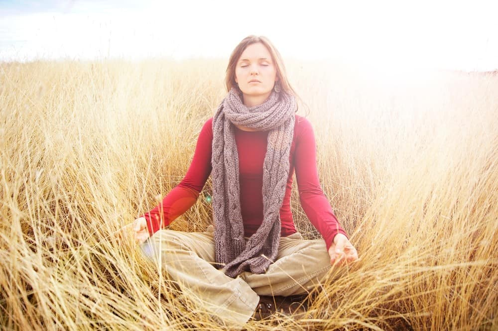 Woman meditating in a field of tall golden grass. Different ways to meditate