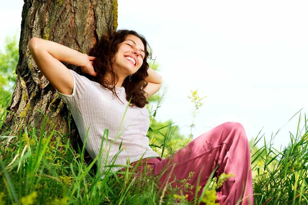 Woman relaxing against a tree, experiencing positive emotions
