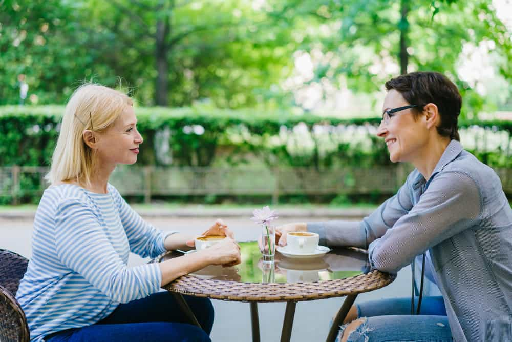 Mature lady talking to friend in open air cafe. smiling and supporting each other