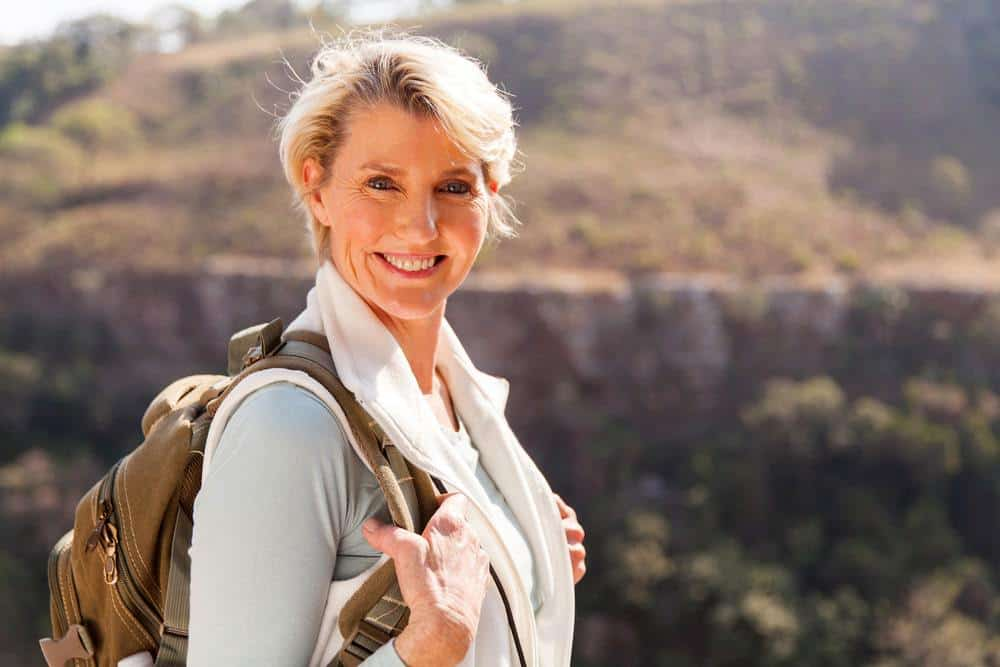 Happy woman with backpack in nature
