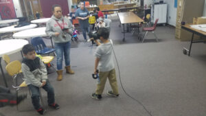 Older students teaching younger ones VR techniques and experiences.