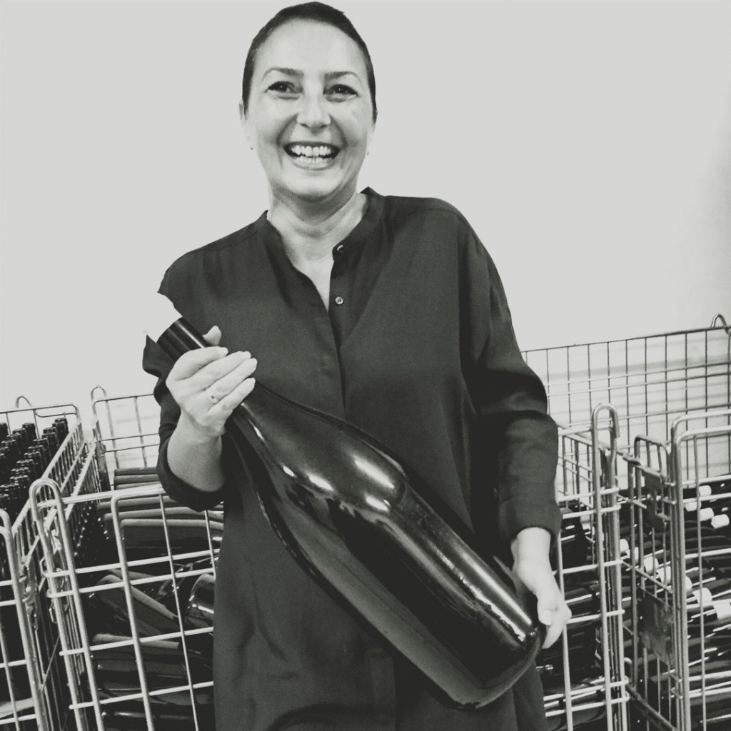 The founder of VinoRoma, Hande Leimer, who is holding an oversized bottle of wine during a visit with members to the cellar of a natural winery.