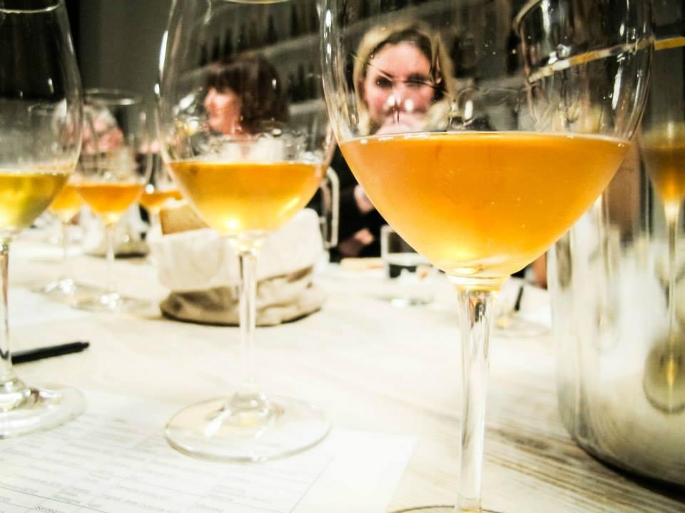 Membri al tavolo di degustazione di VinoRoma che si intravedono attraverso dei bicchieri di vino bianco durante un corso di formazione.