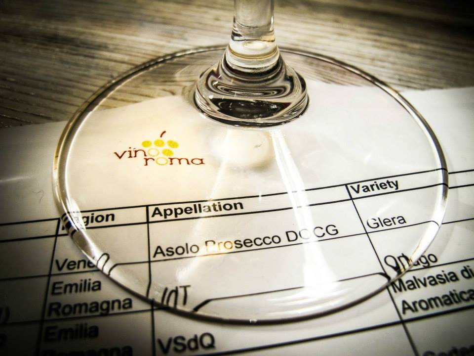 Printed material describing the wines being tasted seen through the base of a wine glass of a member during a tasting.