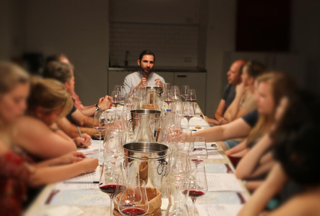 Un sommelier e wine educator spiegando come degustare il vino ai membri seduti al tavolo di degustazione di VinoRoma durante una degustazione.