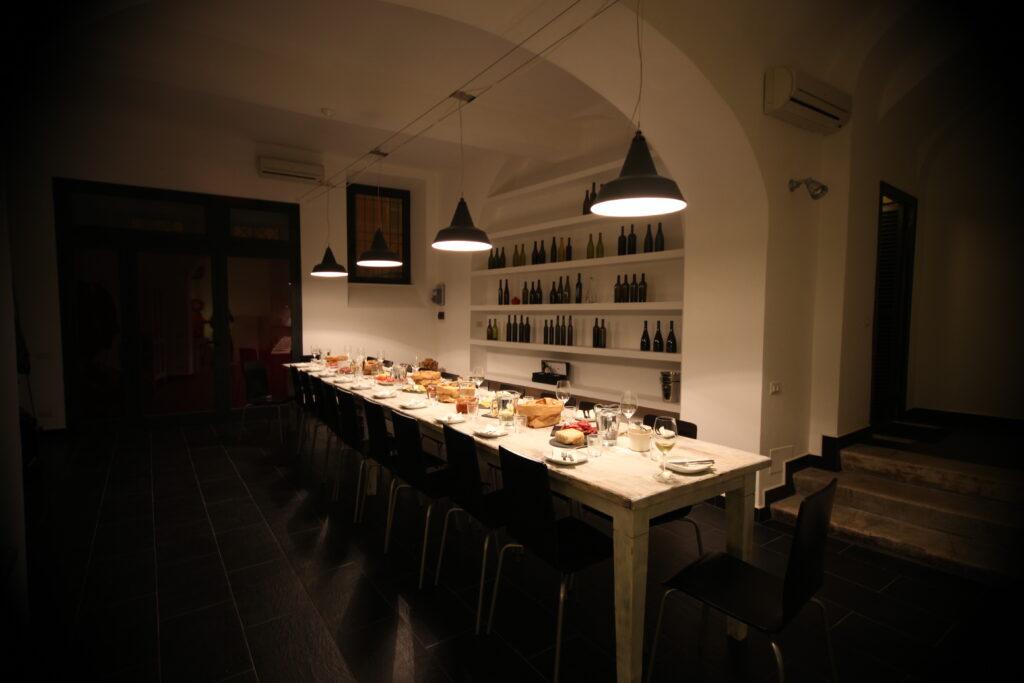 Sala di degustazione di VinoRoma con luce soffusa e il tavolo di degustazione apparecchiato con salumi, formaggi, pane, piatti e bicchieri di vino.