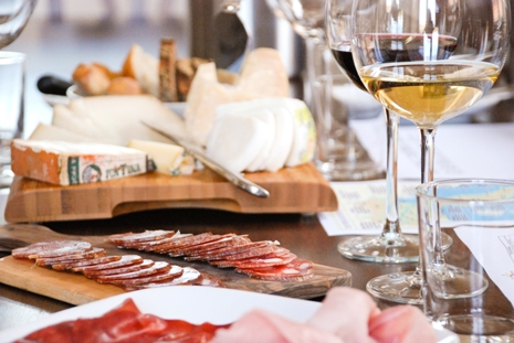 The tasting table set with cured meats, cheeses, glasses with red and white wine and printed material during a tasting.