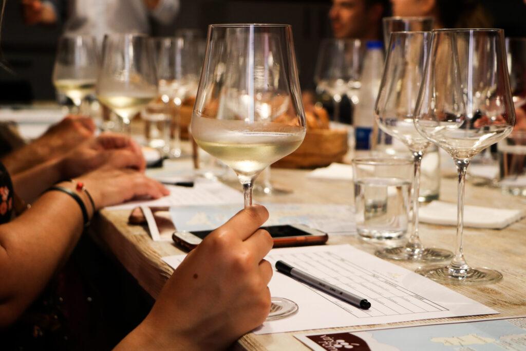 Membri tenendo un bicchiere di vino bianco mentre imparano a degustare il vino durante una degustazione.