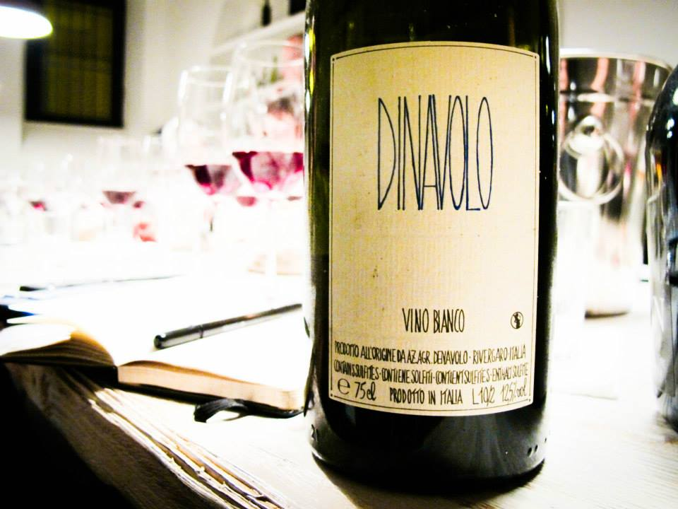 Bottle of natural wine at the VinoRoma tasting table along with open notebook and pen