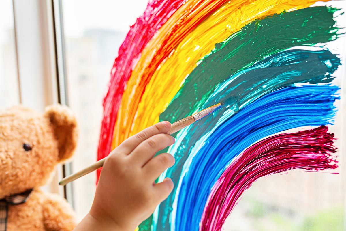child paints a rainbow on a double glazed window symbolising support
