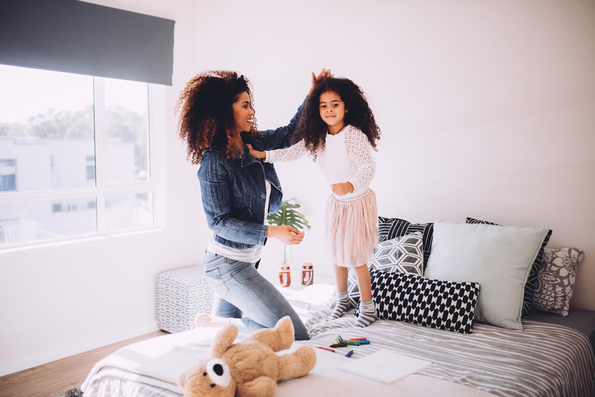 Young mum gets her daughter ready in front of new windows