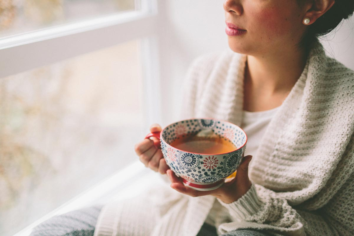 Young woman enjoys a warm drink while looking out her new windows