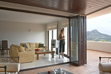 Woman stands in in her home looking out through her sliding patio doors