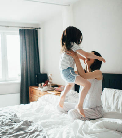 woman lifts her child up in joy while on her bed after a good nights rest