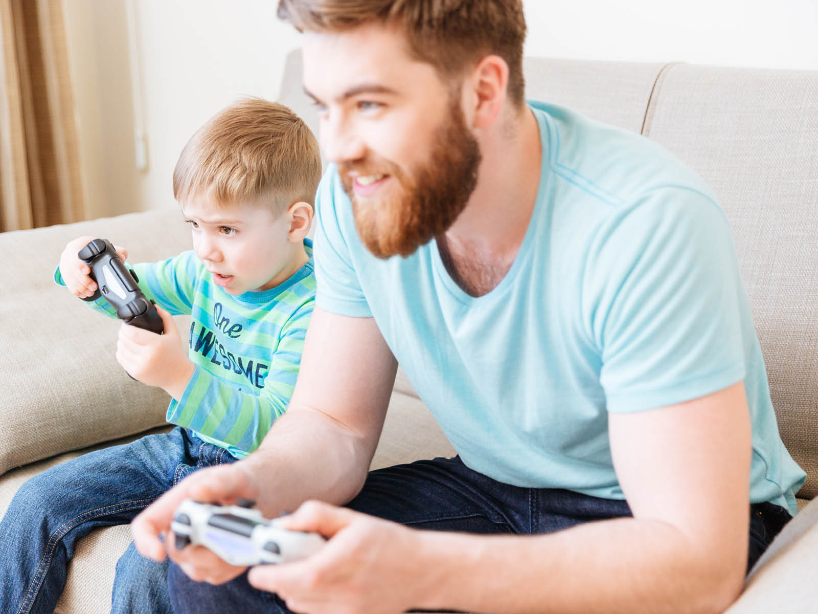 dad and son play some videogames at home