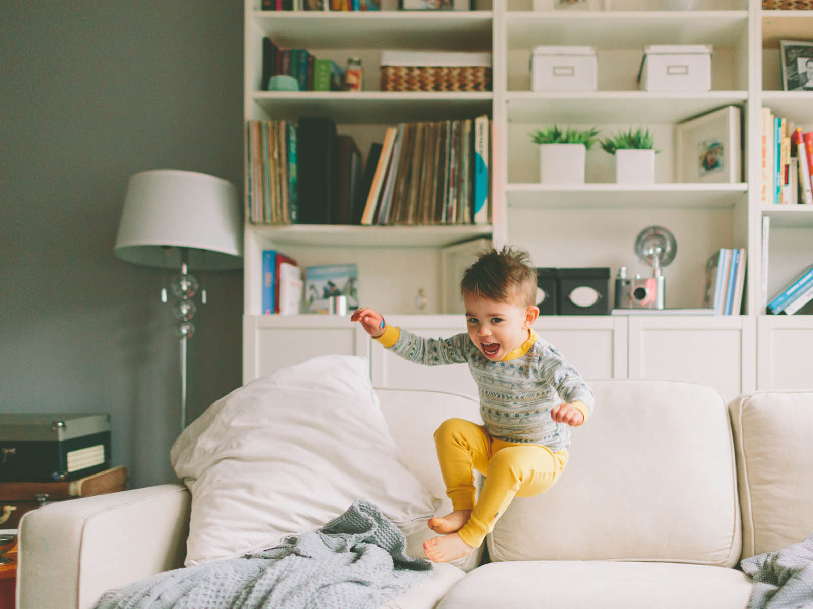 young boys jumps for joy onto sofa