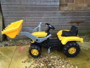 Yellow tractor ride of the toy with large front scoop