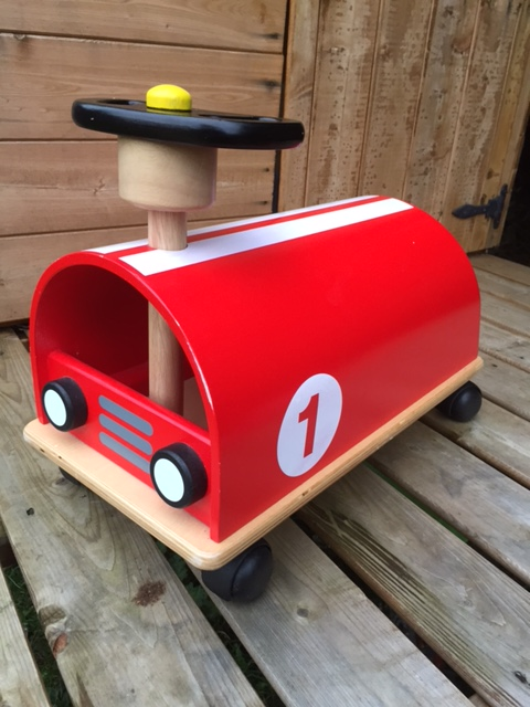 Wooden Car ride on toy, red with white racing stripes and number 1