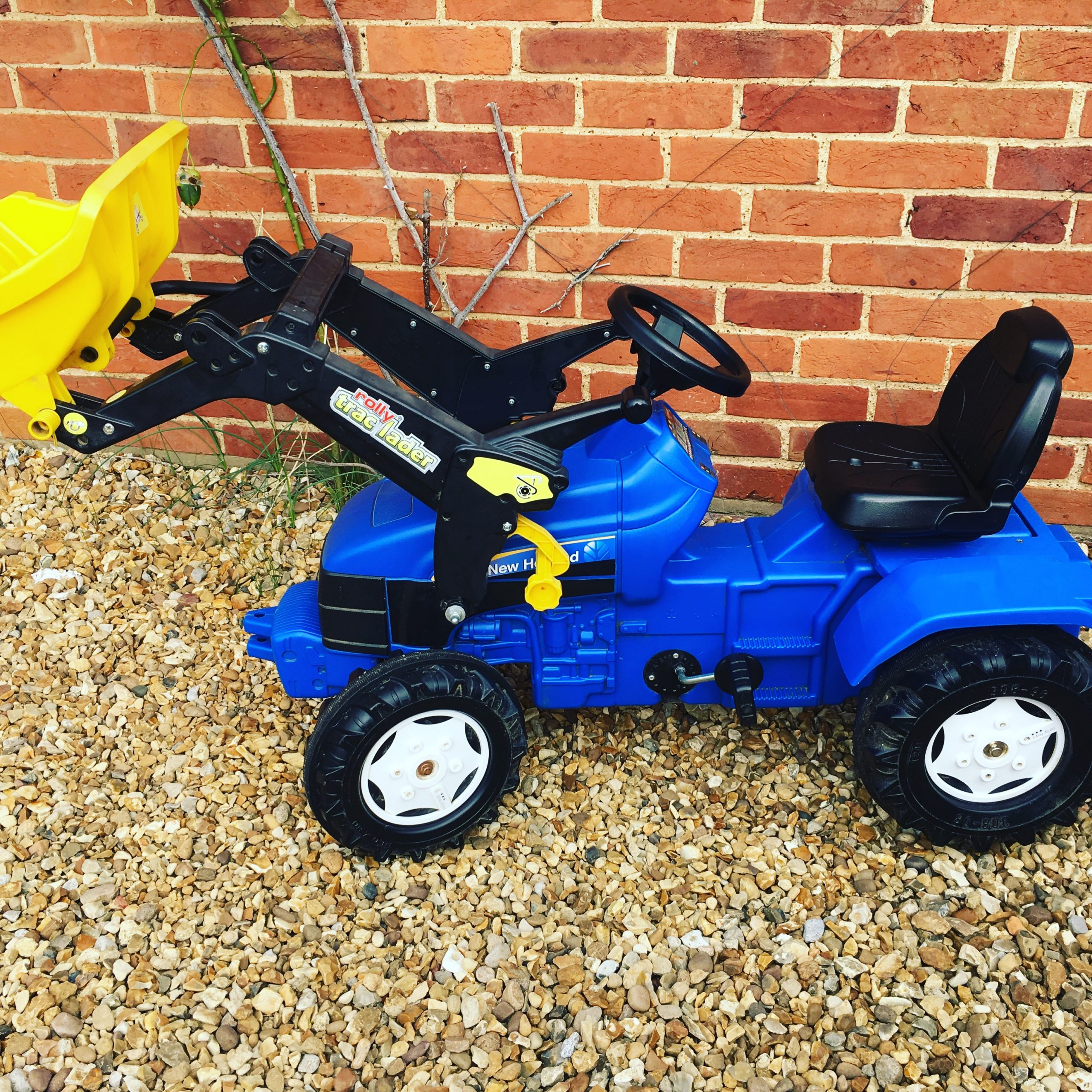 blue and yellow New Holland tractor with front scoop