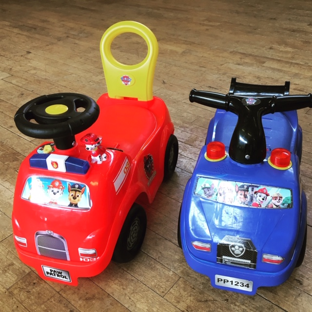 2 Paw Patrol ride-on toys, one blue and one red