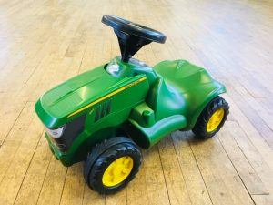 small green John Deere ride on toy tractor