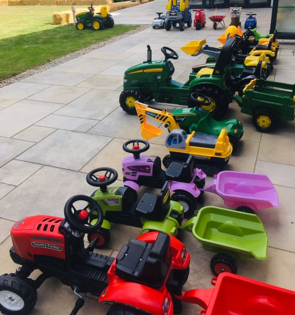 a collection of ride on toy tractors with trailers, in various colours.