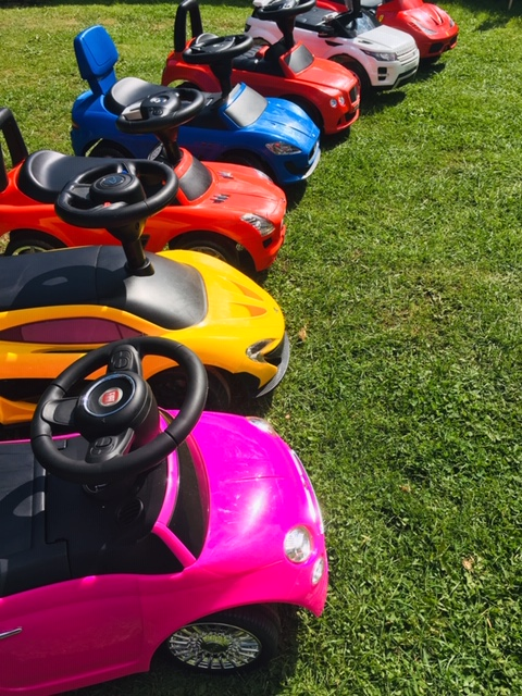 a collection of ride on toy cars in various colours