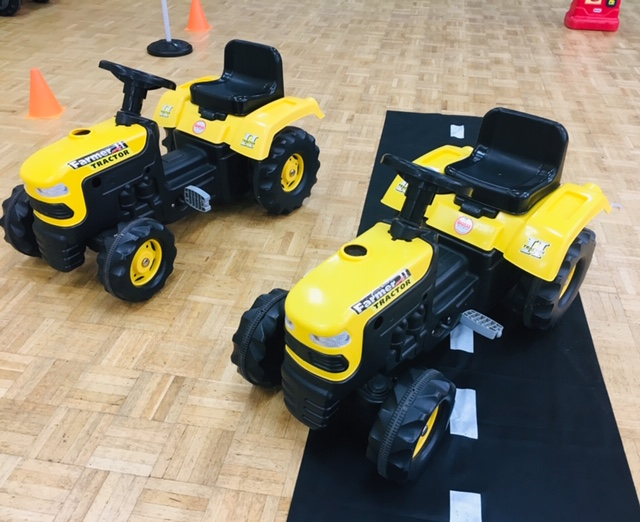 two yellow ride on toy tractors