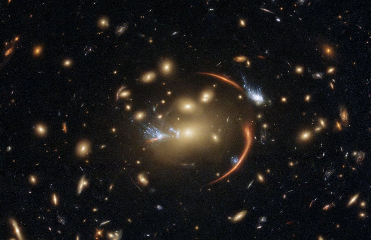 The centre of this image from the NASA/ESA Hubble Space Telescope is framed by the tell-tale arcs that result from strong gravitational lensing, a striking astronomical phenomenon which can warp, magnify, or even duplicate the appearance of distant galaxies. Gravitational lensing occurs when light from a distant galaxy is subtly distorted by the gravitational pull of an intervening astronomical object. In this case, the relatively nearby galaxy cluster MACSJ0138.0-2155 has lensed a significantly more distant quiescent galaxy - a slumbering giant known as MRG-M0138 which has run out of the gas required to form new stars and is located 10 billion light years away. Astronomers can use gravitational lensing as a natural magnifying glass, allowing them to inspect objects like distant quiescent galaxies which would usually be too difficult for even Hubble to resolve. This image was made using observations from eight different infrared filters spread across two of Hubble's most advanced astronomical instruments: the Advanced Camera for Surveys and the Wide Field Camera 3. These instruments were installed by astronauts during the final two servicing missions to Hubble, and provide astronomers with superbly detailed observations across a large area of sky and a wide range of wavelengths. Links  Video of Cosmic Lens Flare