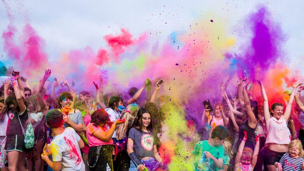 crowd of people throwing colour in the air