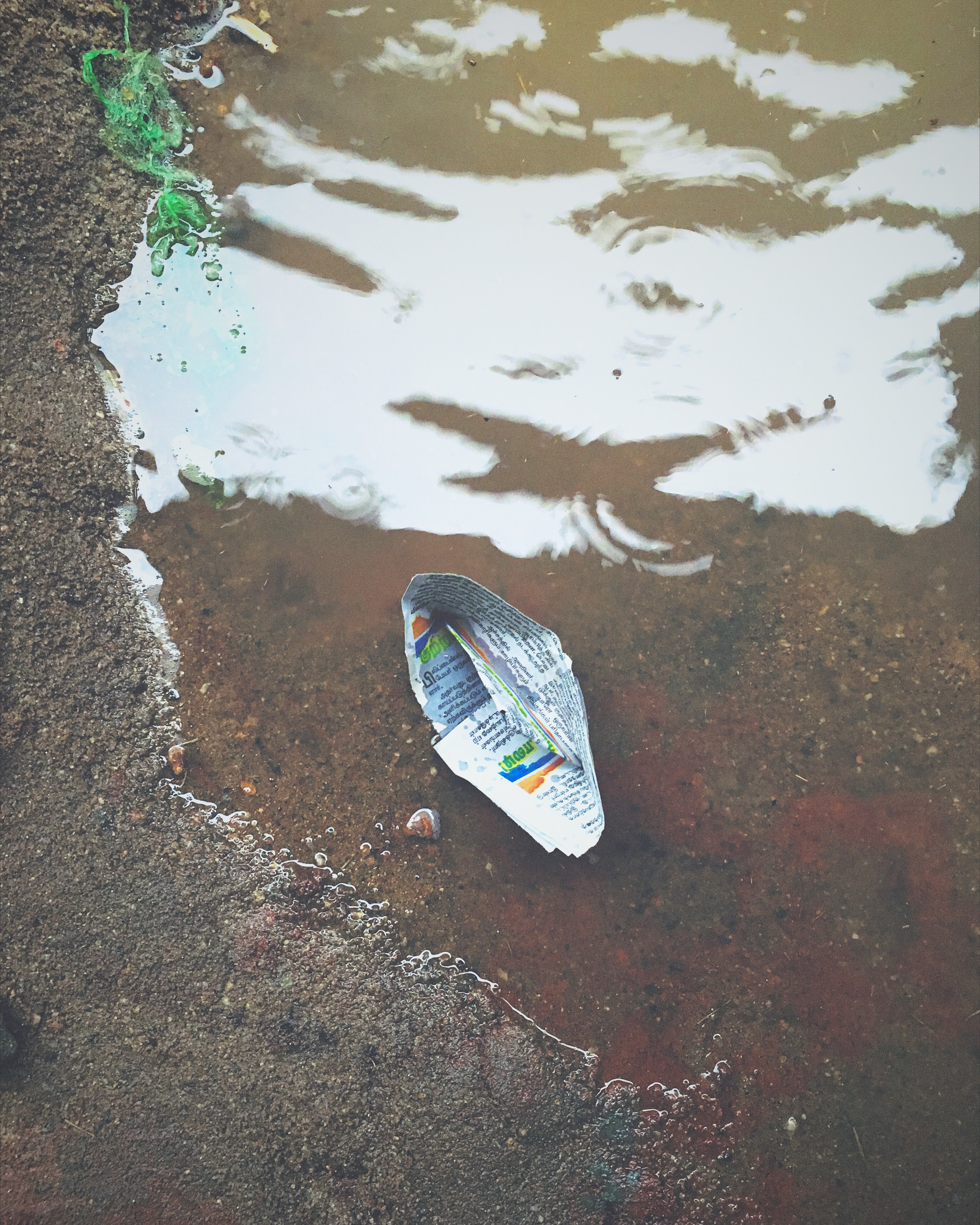 Newspaper Boat Stuck In A Puddle