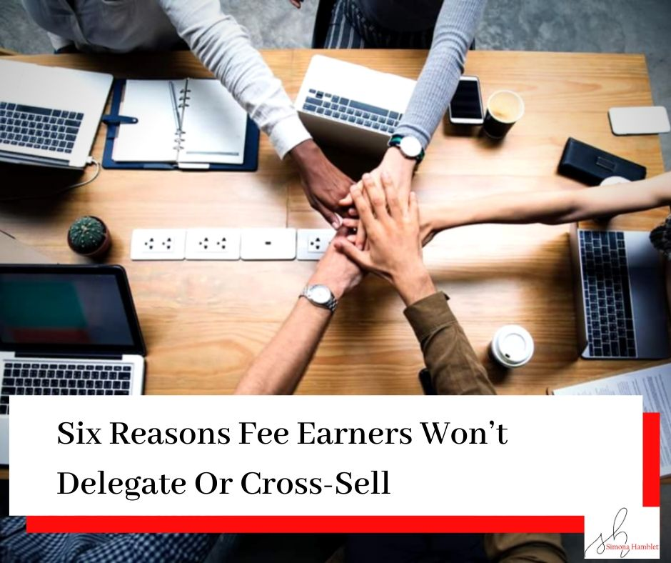 Group of work people putting hands into the middle from a circle around a desk with a title Six Reasons Fee Earners Won't Delegate Or Cross-Sell