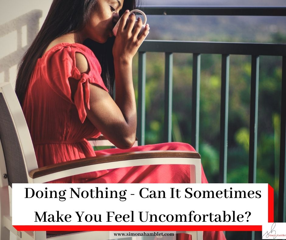 Woman in red sat on a balcony drinking coffee with the title Doing Nothing -Can It Sometimes Make YouFeel Uncomfortable?