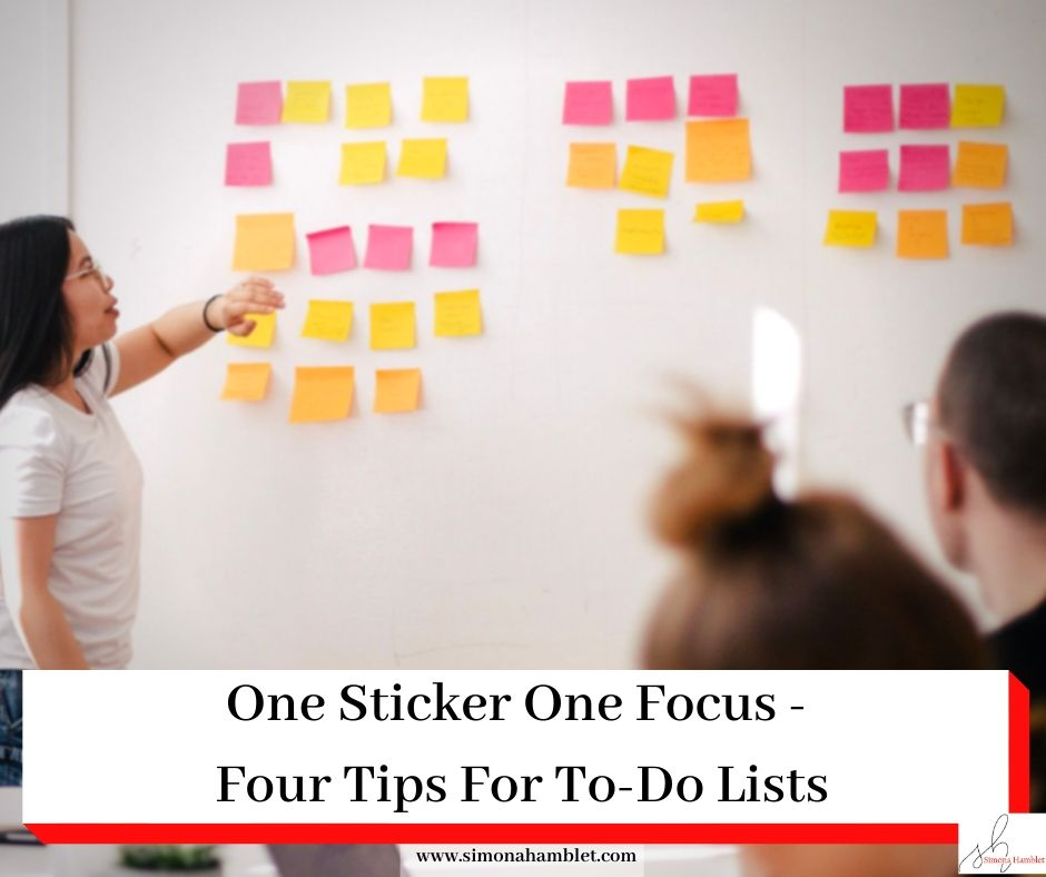 Lady facing a white board with lots of coloured stickers, others sat around a work place desk, with the article title One Sticker One Focus - Four Tips For To-Do Lists