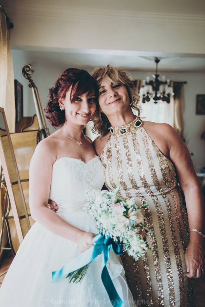 Andreia is wearing a wedding gown on her wedding day, while holding a flower bouquet. She he is hugging her mom