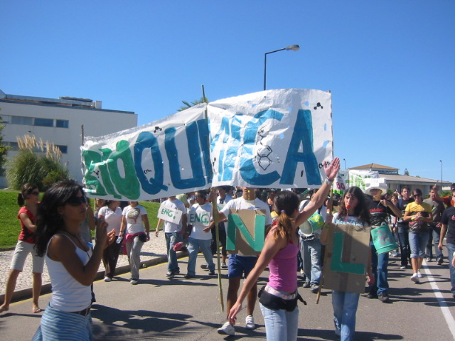 """students hold a banner that reads """"biochemistry"""" in in Portuguese"""