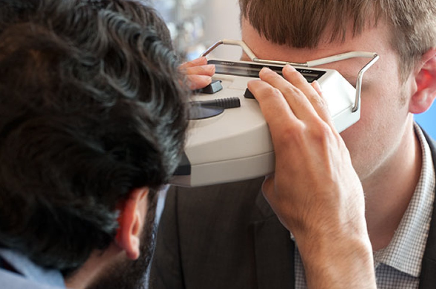 Optician checking boy's eyes with device
