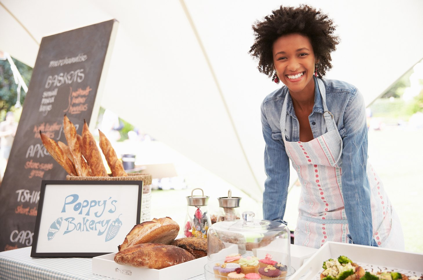 Female bakery employee smiling, leaning on counter with baked goods