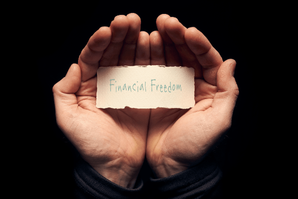 Two hands holding a card saying Financial Freedom