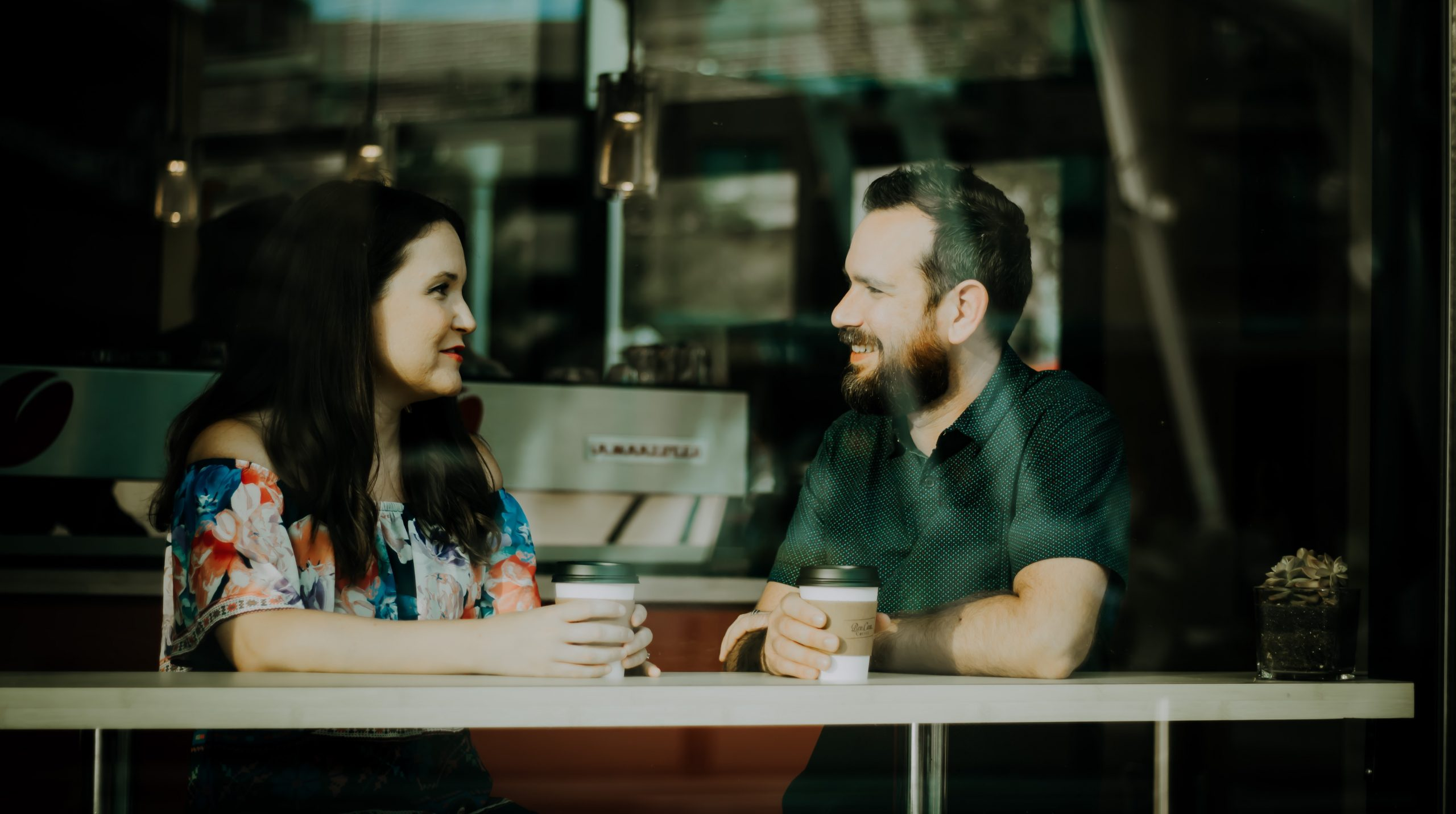 A couple smiling over a cup of coffee at a bench with a La Marzocco coffee machine in the background