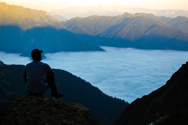 A man in a baseball cap contemplating clouds in a valley below him