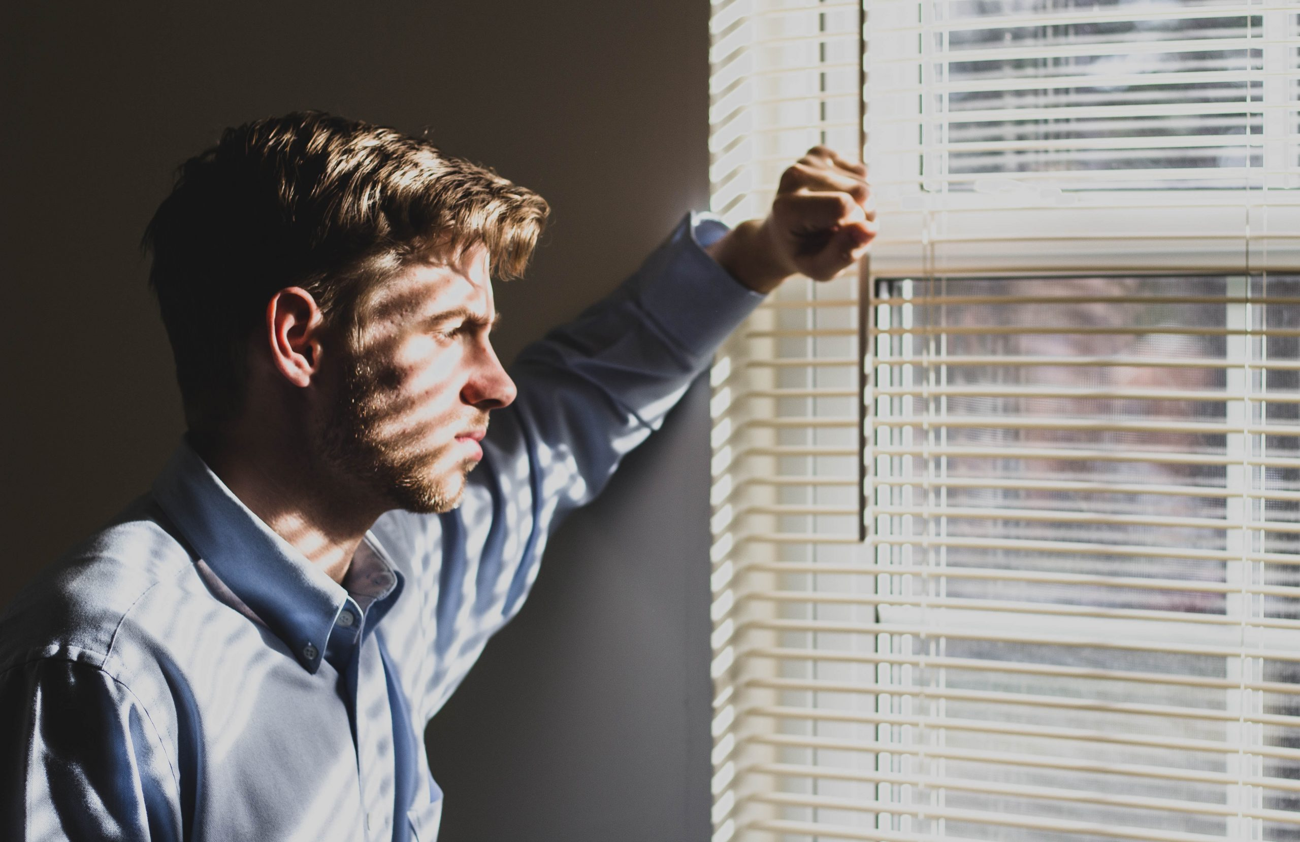 A man looking wistfully out of a window with blinds casting shadows on his face