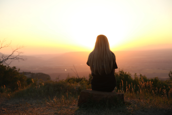 A woman contemplating a sunset over a valley